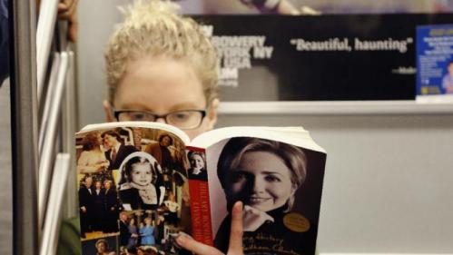 "Linda Leseman reads ""Living History,"" a memoir by Hillary Clinton, while riding the subway, Tuesday, March 1, 2016, in New York. Democratic presidential candidate Hillary Clinton enters a series of Super Tuesday contests poised to extend her lead over Democratic rival Bernie Sanders, who risks a major setback for his insurgent campaign with a poor showing in primaries and caucuses across the nation. (AP Photo/Mark Lennihan)"